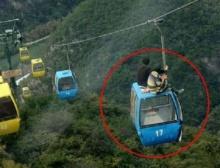 ท้าตาย!! หนุ่มสาวจีนปีนขึ้นไปนั่งบนหลังคากระเช้าลอยฟ้า