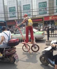 ชายชาวจีนซิ่งพาหนะสองล้อลูกผสมระหว่างเก็ตบอร์ดและจักรยานได้อย่างคล่องแคล่ว