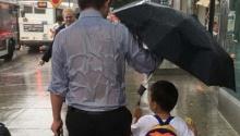 ซุปเปอร์แด๊ด! ชาวเน็ตยกนิ้ว คุณพ่อกางร่มให้ลูกชายจนตัวเปียกปอน